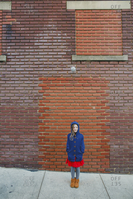 Girl standing in front of a brick building