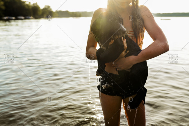 Young woman holding a wet dog on the shore of a lake