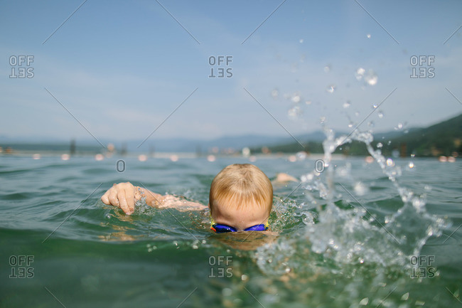 Little boy with goggles swimming in a lake
