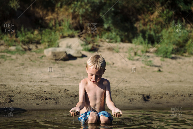 Boy playing with sand in a shallow river