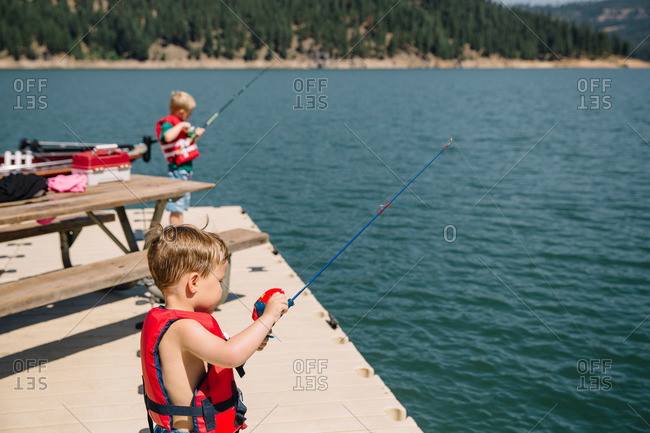 Little boys fishing in a lake from a pier