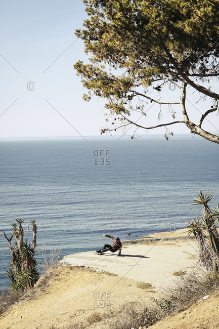 Young man falling off a skateboard by the ocean