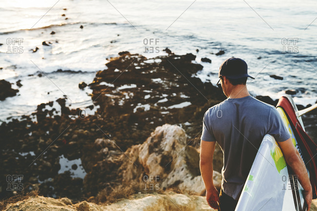Young man looking at the ocean holding surfboard