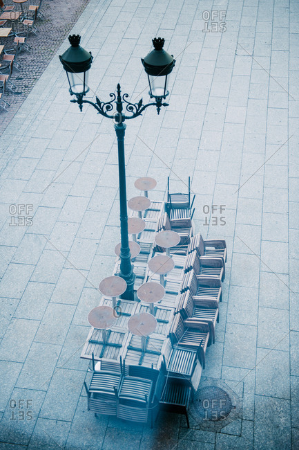 Tables and chairs arranged near a street lantern