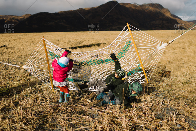 Kids playing in hammock in field