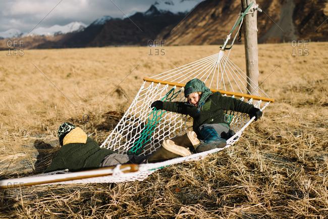 Two kids on hammock in field
