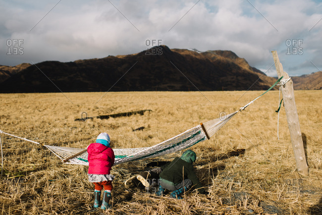 Kids playing on hammock in field