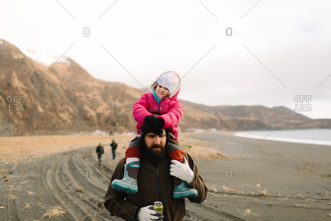 Dad carrying girl on rural coast
