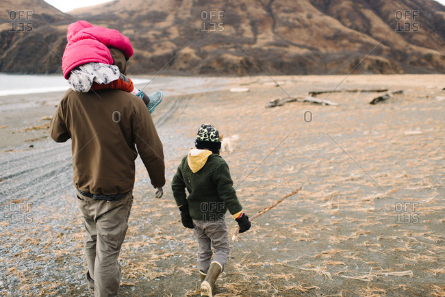 Dad walking with kids on rural coast