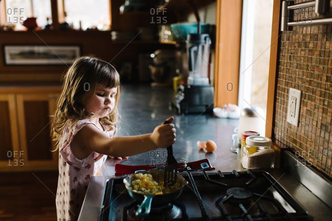 Girl at counter making scrambled eggs