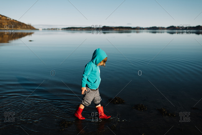Kid wading in water in rain boots