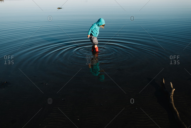 Kid wading in water in boots