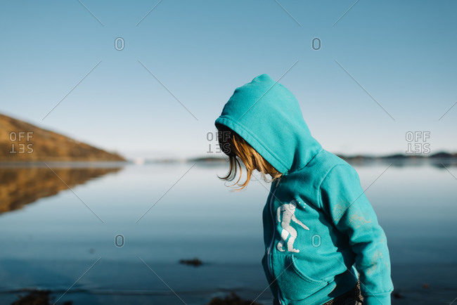 Kid in sweatshirt standing in lake