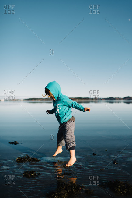 Kid in sweatshirt jumping over lake
