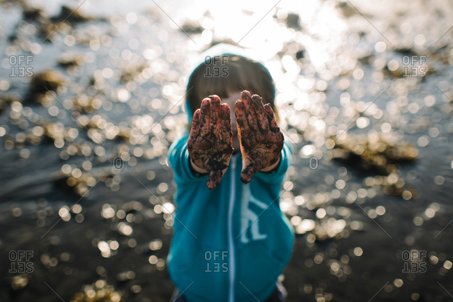 Kid with muddy hands in lake