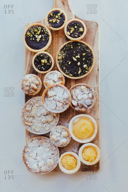 Miniature pies and tarts on a wooden cutting board
