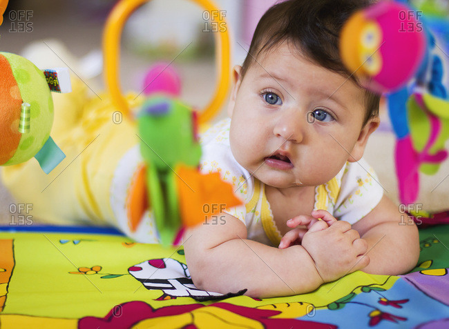 Adorable chubby cheeked baby staring at toys while lying on play mat