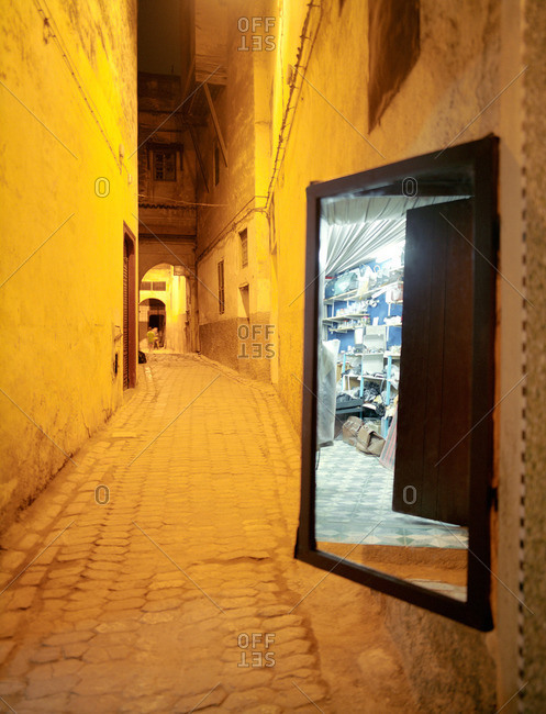 Mirror by store in Moroccan alleyway
