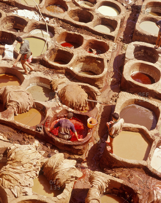 Workers tan leather in pits, Morocco