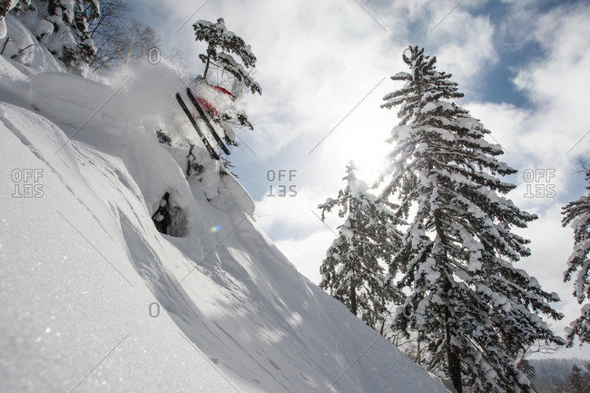 Skier flying of a jump on steep trail