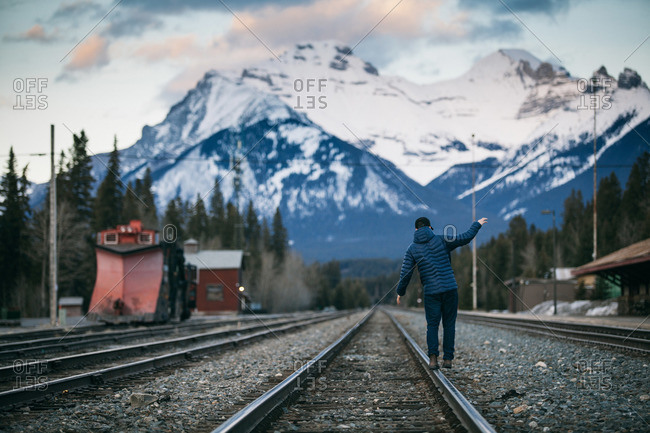 Man balancing on train tracks in a mountain valley
