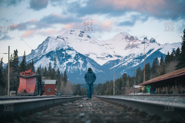 Man walking on train tracks in a mountain valley