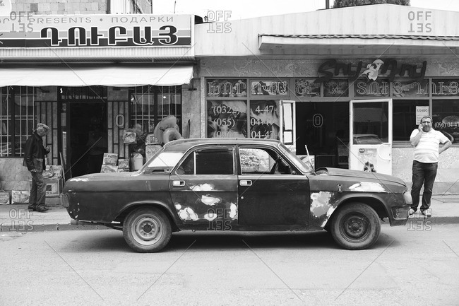 Spitak, Armenia - July 9, 2013: Vintage car with patches on a street in front of a market