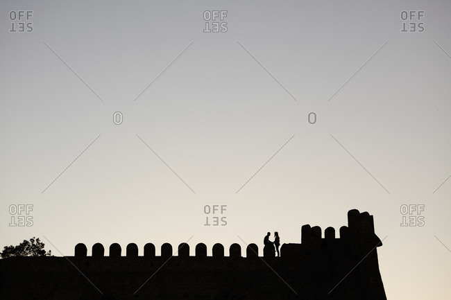 Silhouettes of a couple on an ancient fortress wall at sunset