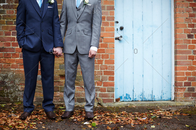 Two grooms hold hands outside a brick building on their wedding day