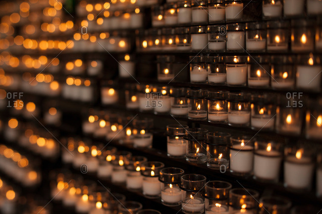 Rows of lit votive candles in a church