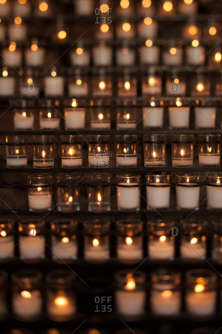 Many votive candles lit in a church