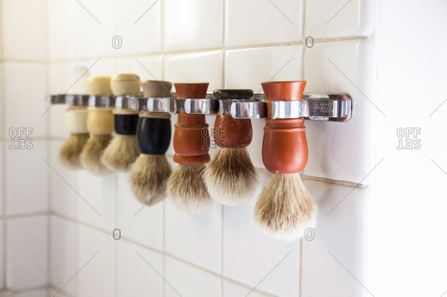 Row of shaving brushes hanging on a tile wall