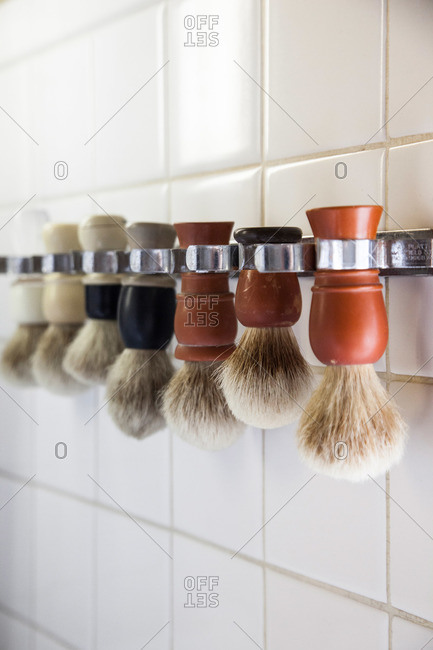 Many shaving brushes lined up and hanging on a wall