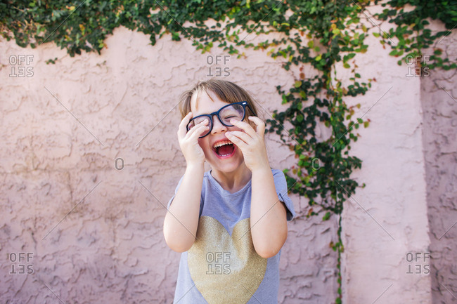 Laughing young girl tries on pair of eyeglasses