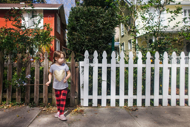 Young girl standing on sidewalk in front of picket fence