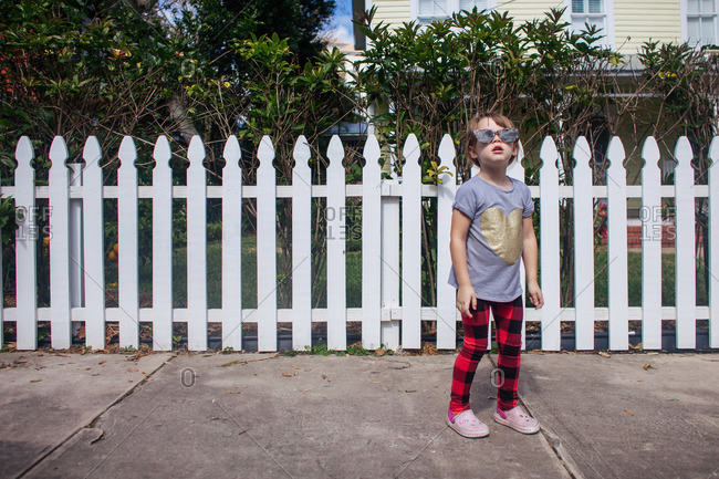 Young girl in sunglasses standing on sidewalk in front of picket fence