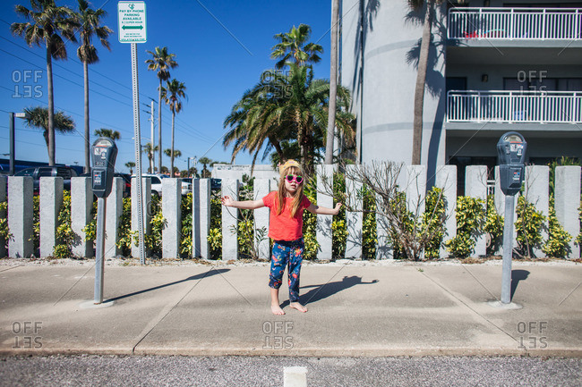 Young girl in sunglasses standing barefoot on sidewalk between two parking meters