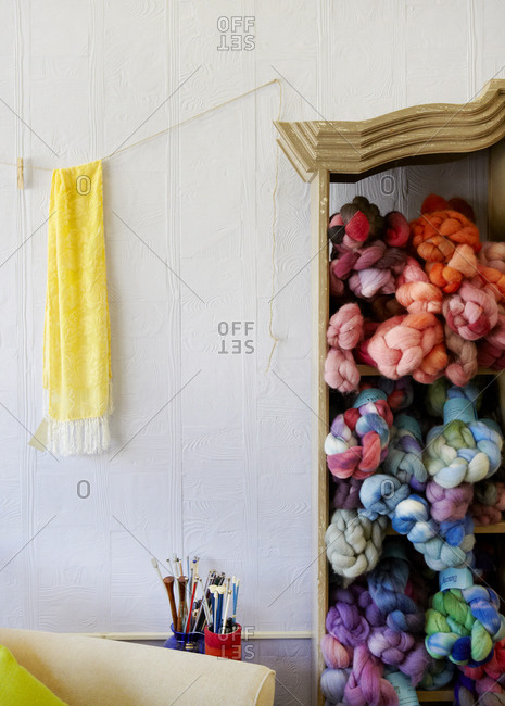 Yarn in a cabinet and a scarf hanging on the wall