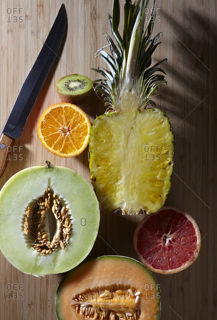 Halved fruit with a knife on a wood table
