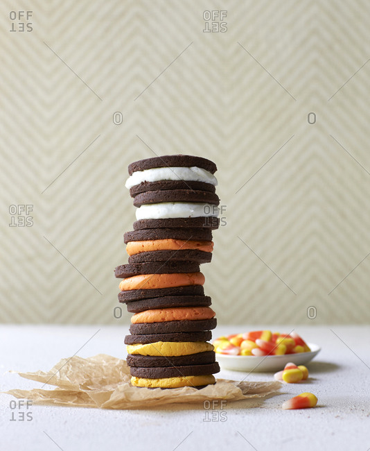 A stack of homemade Halloween sandwich cream cookies and a dish of candy corn