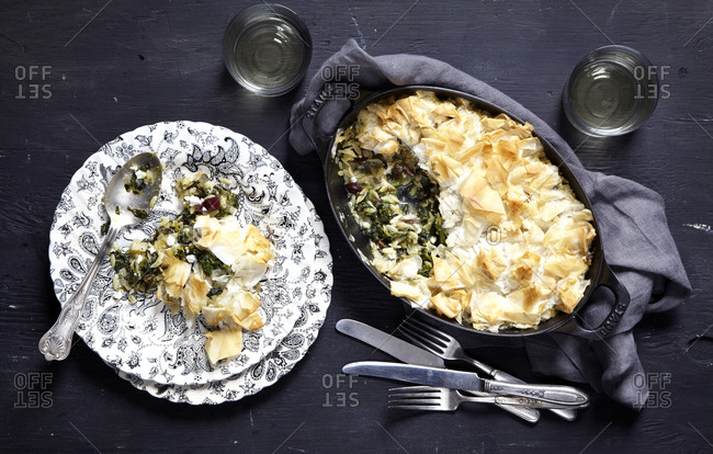 Spinach orzo pie served in cast iron cookware