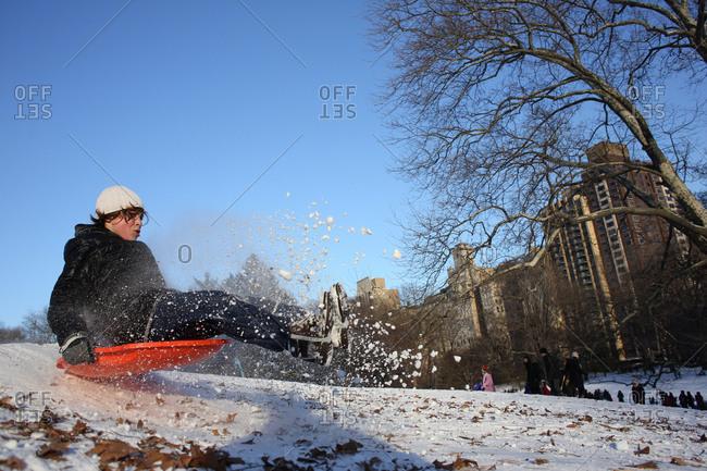 New York City, NY - January 4, 2014: Boy sledding in Central Park in New York City
