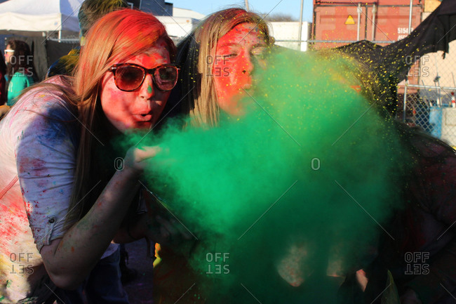 New York City, NY - April 6, 2013: Participants blowing colorful powder during the Festival of Colors Holi NYC event at the Cultural Performing Arts Center, Brooklyn, New York
