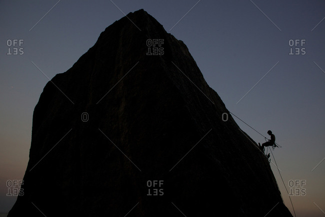 Silhouette of rock climber climbing around Sugar Loaf Mountain, Rio de Janeiro, Brazil