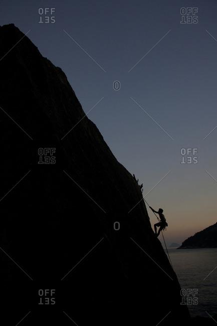 Silhouette of person rock climbing around Sugar Loaf Mountain, Rio de Janeiro, Brazil