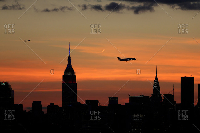 The sun setting behind the Manhattan skyline in New York City viewed from Flushing, Queens, New York