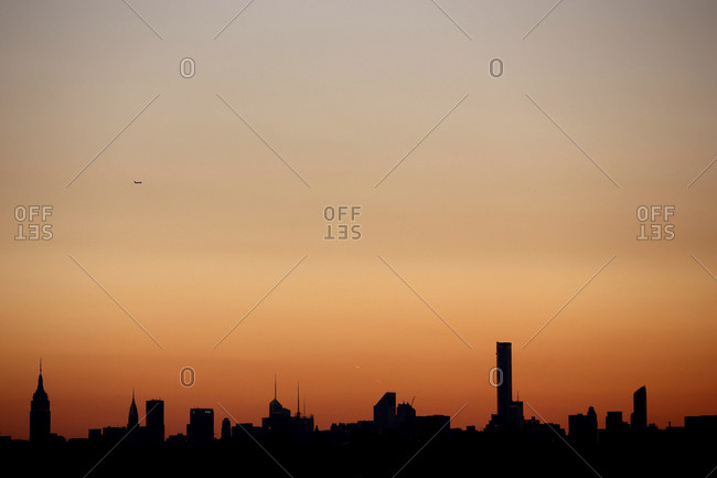 The sun setting in the Manhattan skyline in New York City viewed from Flushing, Queens, New York