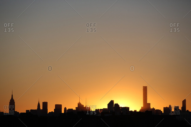 Viewed of the sun setting behind the Manhattan skyline from Flushing, Queens, New York