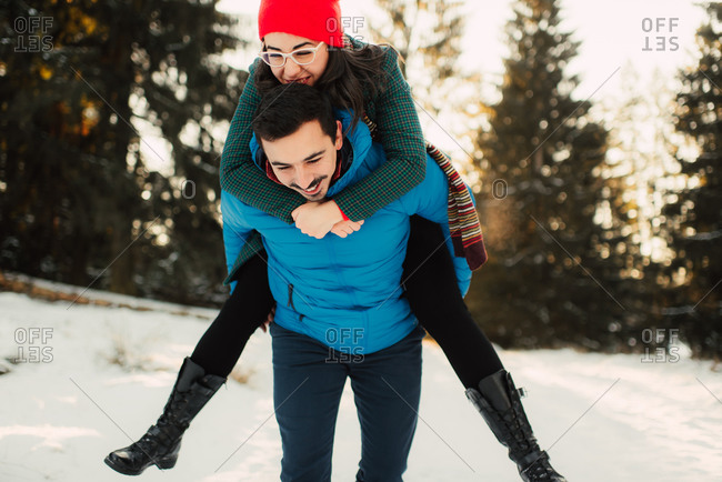 Young woman riding piggyback with her fiance in the cold