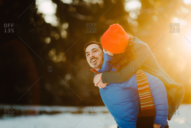 Young man carrying his fiancee on his back in the cold